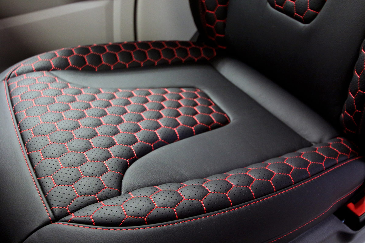 Close-up of leather seat showing red stitching
